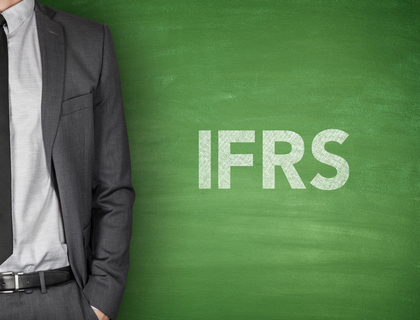 A picture of a business man standing in front of a chalkboard that says IFRS