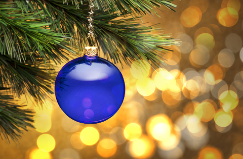 A blue glass bauble hanging from a pine tree branch
