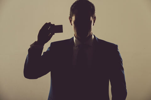 A business man in shadow holding a business card