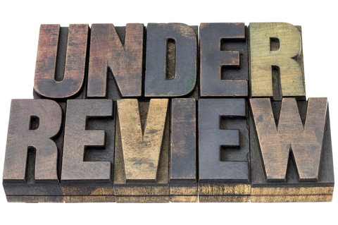 A picture of vintage letterpress wood type that says Under Review
